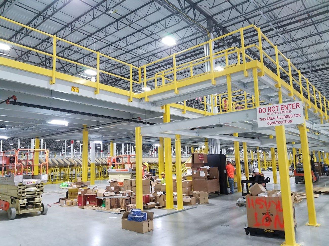 四个戴安全帽的人在工业运输仓库工作,用不锈钢平台和楼梯组织