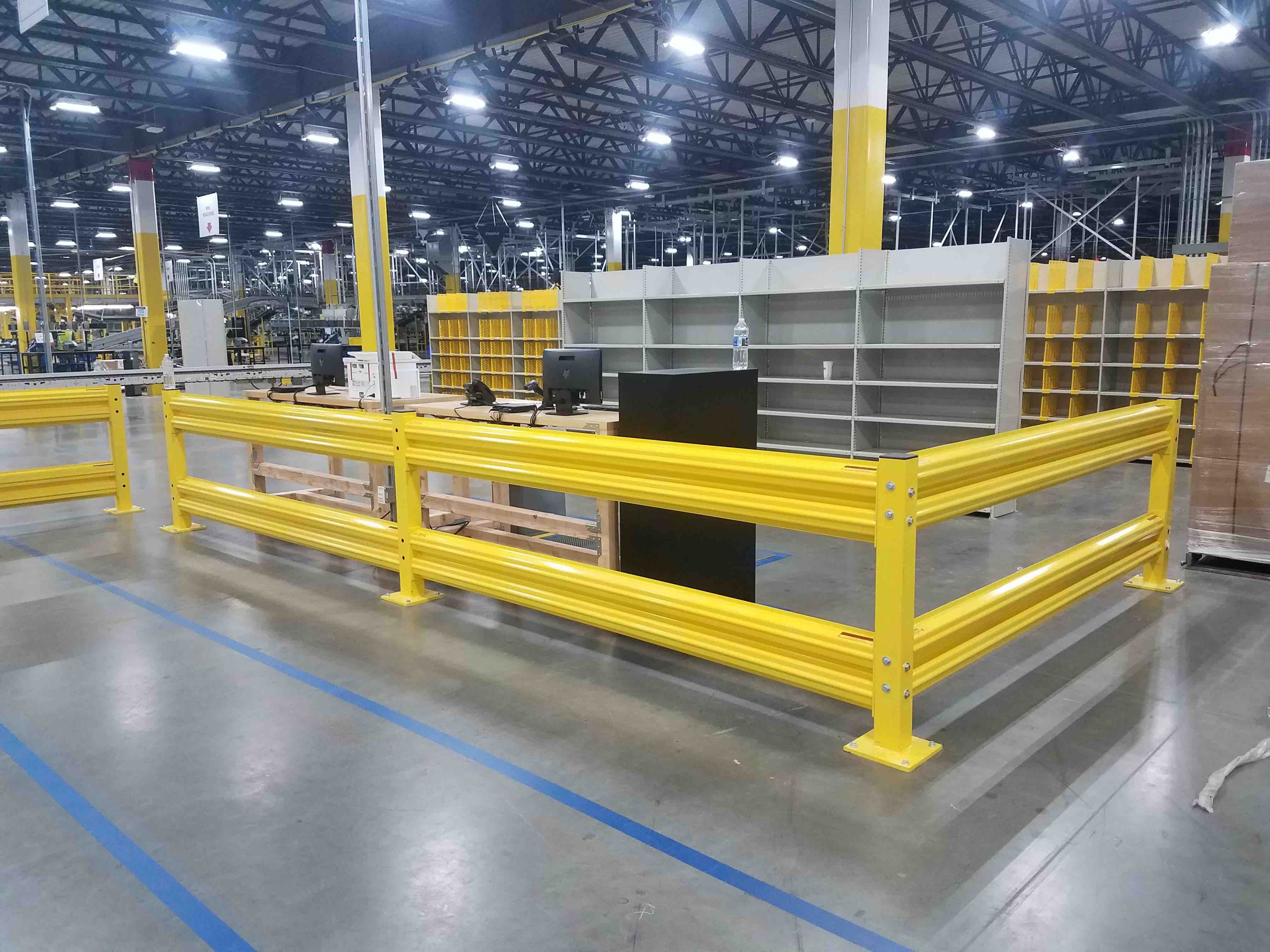 OSHA tall yellow safety rail protecting desk with computers from shipping warehouse floor