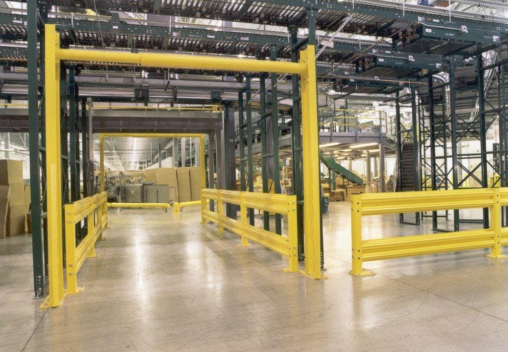 OSHA yellow steel safety rails under green mezzanines in warehouse